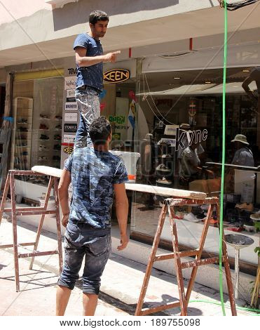 31ST MAY 2017, FETHIYE, TURKEY: Unknown turkish builders plastering a shop front in an unsafe way with no personal protection equipment in fethiye, turkey,31st may 2017