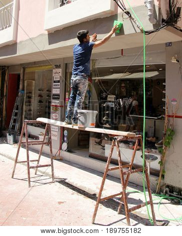 31ST MAY 2017, FETHIYE, TURKEY: An unknown turkish builder plastering a shop front in an unsafe way with no personal protection equipment in fethiye, turkey,31st may 2017