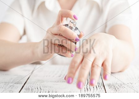 woman sprinkle perfume on her wrist on table
