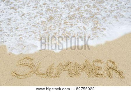 Sign Summer on the sandy beach near ocean