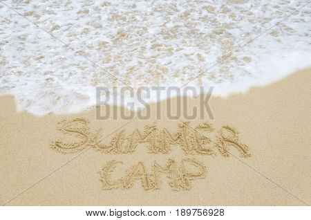 Sign Summer Camp on the sandy beach near ocean