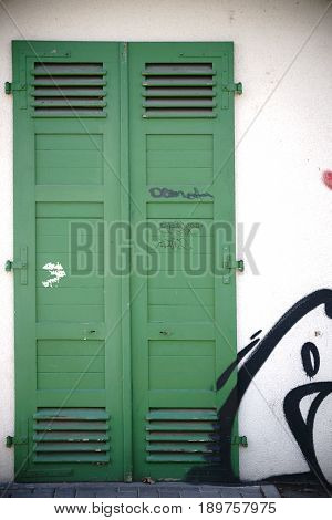 Green painted and nostalgic door with ventilation slots.