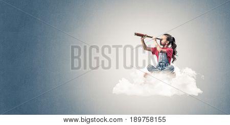 Cute kid girl on cloud looking in spyglass