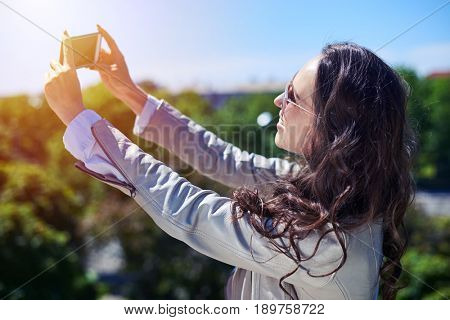 Mid shot of fantastic madam taking selfie in front of city panorama