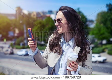 Mid shot of graceful woman looking on smartphone and holding cup of coffee