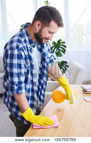 Vertical of delightful male pulverizing and dusting working place