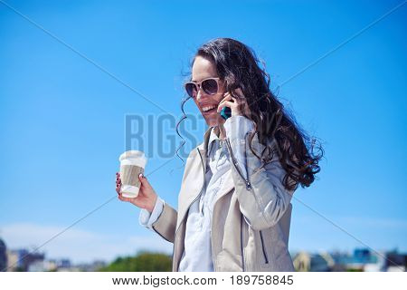 Mid shot of good-looking madam talking on phone while drinking coffee on top of building
