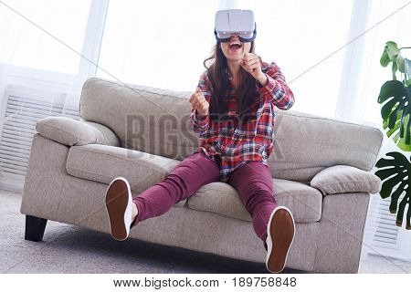 Wide shot of female wearing VR glasses driving car in virtual reality with copy space