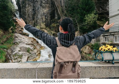 BAD GASTEIN, AUSTRIA - 22 APRIL 2016:  Girl traveler with a backpack near the Alpine falls