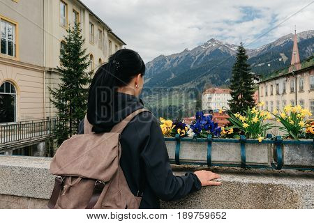 BAD GASTEIN, AUSTRIA - 22 APRIL 2016: A traveler with a backpack is standing on a bridge overlooking the Alpine mountains