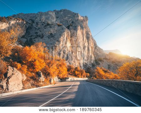 Asphalt road in autumn at sunrise. Landscape with beautiful empty mountain road with a perfect asphalt high rocks trees and sunny sky. Vintage toning. Travel background. Highway at mountains. Nature