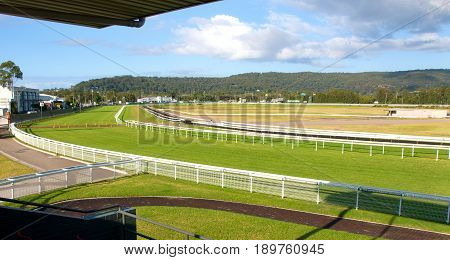 Racecourse panorama of a country Australian Grass racecourse with green grass white fences and white cloud in a blue sky. Situated at Gosford New South Wales Australia