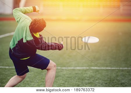 Guy with the team is throwing throwing and catching with flying disk at the sports stadium. Concept of the game is active and mobile in summer. Sunny highlight. Disk for throwing