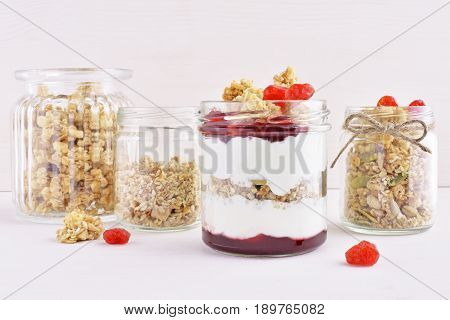 Greek natural yogurt with dry cherry and wholegrain granola in small jars against white wooden background