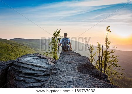 Man Tourist Sitting On Top Of Hill At Sunrise