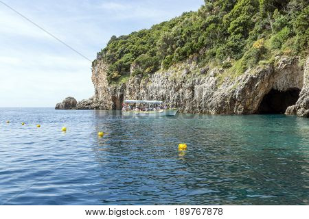 PALEOKASTRITSA, GREECE - MAY 15: Tourists on the boat visit the caves on the Ionian Sea coast on May 15, 2017 in Paleokastritsa resort, Corfu island in Greece.