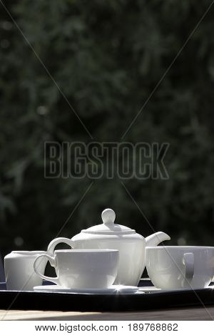 Afternoon tea set in an English country garden. White porcelain teapot cups and sauces on a garden furniture table in summer sunshine.