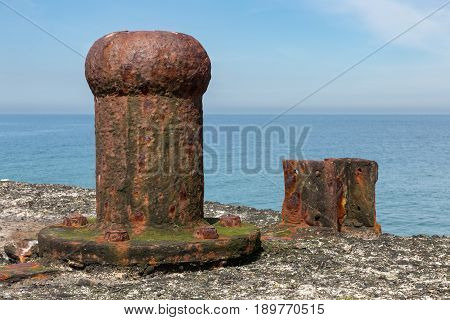 Old decayed and rusty bollard at Dune small island near Helgoland in German Northsea