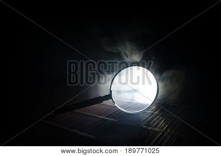 Close Up Single Magnifying Glass With Black Handle, Leaning On The Wooden Table On Orange Red Smoke