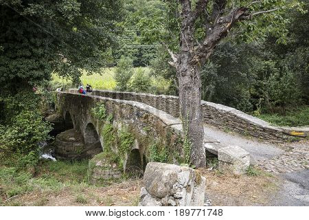 pilgrims on the Ponte Aspera medieval bridge over Pequeno river, Sarria, province of Lugo, Galicia, Spain