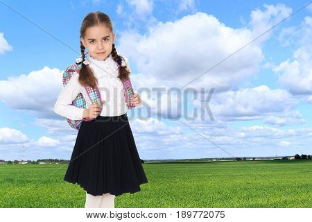 Beautiful little blond schoolgirl, with long neatly braided pigtails. In a white blouse and a long dark skirt.She wears a school satchel.On the background of green grass and blue sky with clouds.