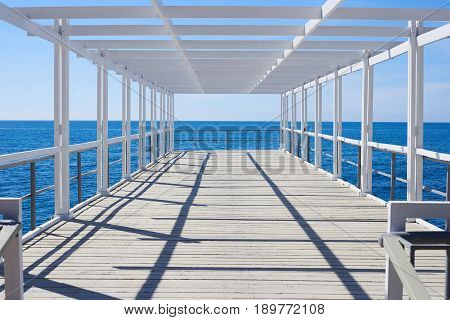 old wooden pier with wooden white frame on ocean seaside in middle summer day with deep shadows on the floor. Outdoor travel and wedding concept.