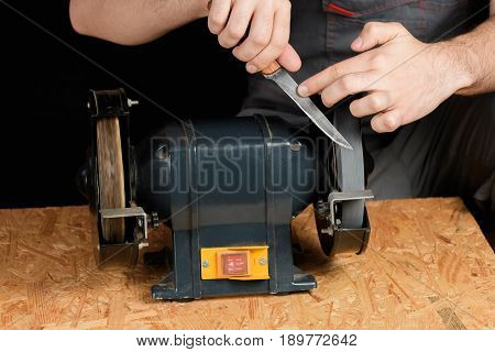A Man In Working Clothes Hones Professional Sharpening Kitchen Knive On The Table