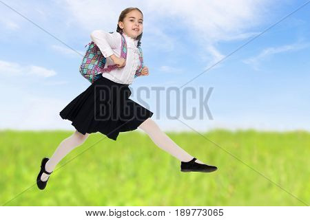 Beautiful little blond schoolgirl, with long neatly braided pigtails. In a white blouse and a long dark skirt.She jumps over the obstacle.On the background of green grass and blue sky with clouds.