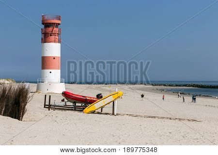 HELGOLAND GERMANY - MAY 20 2017: Lighthouse and tourists watching grey seals at beach of Dune