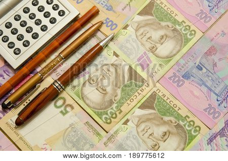 A calculator, a pencil and two fountain pens lie on denominations of five hundred and two hundred hryvnia.