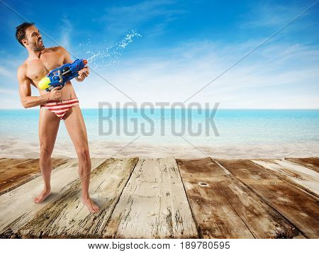 Boy play with water gun at the beach