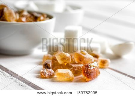 lumps of white and brown sugar on white wooden kitchen table background