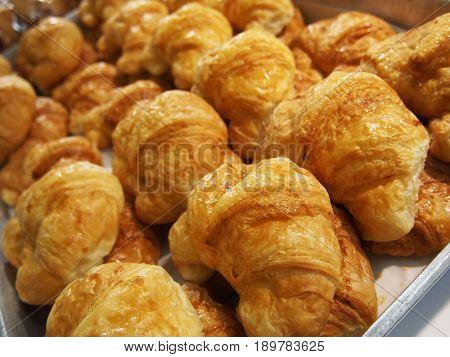pile of croissants in on shelf in bakery or baker's shop