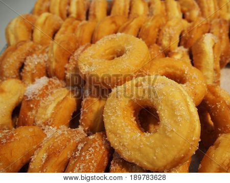 pile of donuts in on shelf in bakery or baker's shop