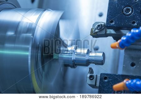 The CNC lathe machine or Turning machine cutting the metal rod with the lathe tool .The hi-technology machining concept.