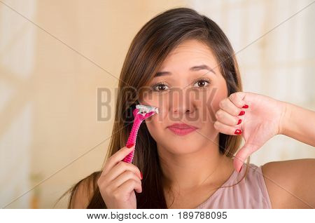 Close up of a beautiful young funny woman with an shaver on her face with a thumps down.