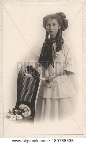 HARRISON, IDAHO, USA - CIRCA mid-1910s: Vintage portrait of a young girl in ringlet curls holding a diploma
