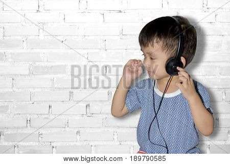 Happy smiling child enjoys listens to music in headphones. Listening Music Studio Concept.