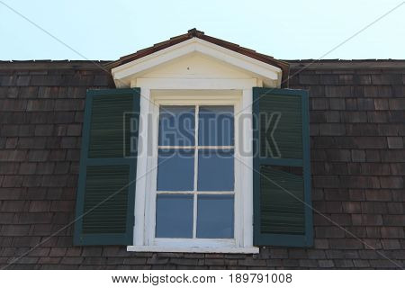 White paned window with dark green wooden shutters against a roof with dark brown shingles