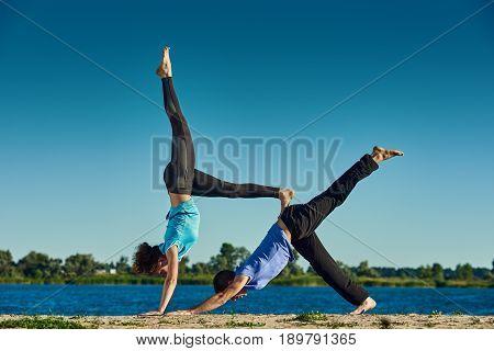 Two person balancing pose Eka Pada Adho Mukha Svanasana