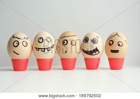 Eggs With Painted Face. Concept Of The First