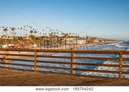 OCEANSIDE, CALIFORNIA - MARCH 23, 2017:  The names of donors carved into the railings of the historic fishing pier, with the beach and ocean in the background.