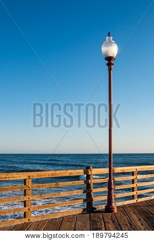 OCEANSIDE, CALIFORNIA - MARCH 23, 2017:  A lamp at dusk on the landmark fishing pier, with names of donors carved into the pier railings.