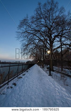 Snow pathway and light pole next to lake with sunset