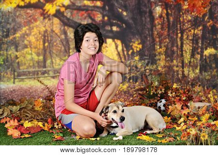 A young teen girl kneeling by her dog after romping with a soccer ball on a warm fall day.
