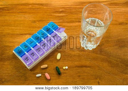 Daily Pillbox, Pills & Glass Of Water On Wood Background