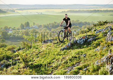 Young cyclist riding the bike on the rocky trail against beautiful landscape. Sportsman wearing black sportwear and sportive shoes. Extreme travelling in the countryside. Concept of the active and healthy lifestyle.