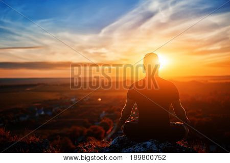 Rear view of the man meditating yoga in lotus pose on the rock at sunset. Horizontal photo. Beautiful landscape with sky and clouds like a background. Concept of the healthy and active lifestyle.