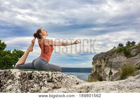 Young woman doing yoga exercise pigeon asana on the rock against river. Sporty woman in the t-shirt, leggings and barefoot. Horizontal photo. Beautiful landscape with sky, clouds, rock, tree, river like a background. Concept of the healthy lifestyle.