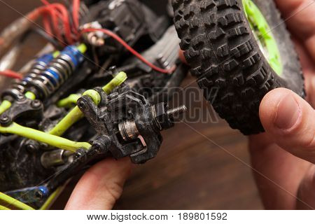 Rc radio control car crawler model whell repair on wooden background. Green toy suv in repairshop workplace, free space
